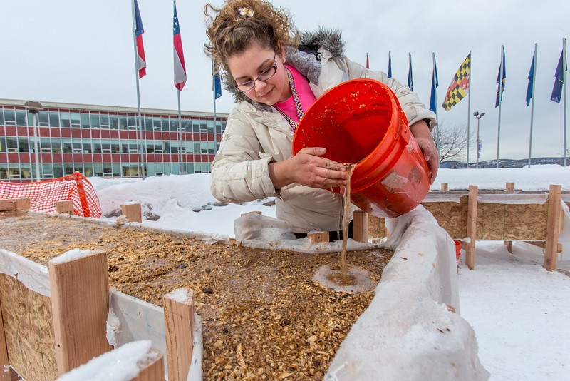 "Civil engineering major Katrina Monta adds water to a mixture combined with sawdust which when frozen, hardens into a substance many times stronger than concrete. Katrina and others are hard at work on this year's traditional ice arch, designed and built each year by engineering students.  <div class=""ss-paypal-button"">Filename: AAR-13-3727-23.jpg</div><div class=""ss-paypal-button-end"" style=""""></div>"