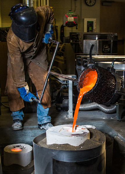 "Art major Joel Isaak fills a mold with molten bronze as part of the process of creating a life-sized sculpture for his senior thesis in the UAF Fine Arts complex.  <div class=""ss-paypal-button"">Filename: AAR-12-3347-096.jpg</div><div class=""ss-paypal-button-end"" style=""""></div>"