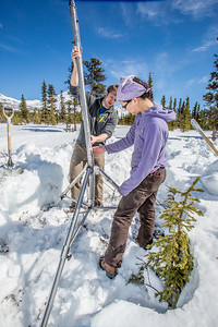 Daisy Huang, right, a research engineer for the Alaska Center for Energy and Power, works with ACEP intern Luke George to install a meteorological station on a hillside near the Black Rapids Lodge, about 150 miles southeast of Fairbanks. The station will record wind speed and direction, as well as temperatures at different altitudes.  Filename: AAR-13-3843-74.jpg