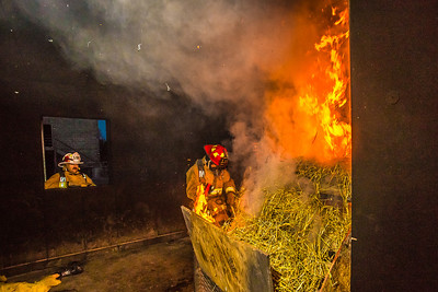 UFD Captain Ben Fleagle sets fire to a mix of straw and scrap lumber during a live training drill at the Fairbanks Fire Training Center.  Filename: AAR-13-3978-46.jpg