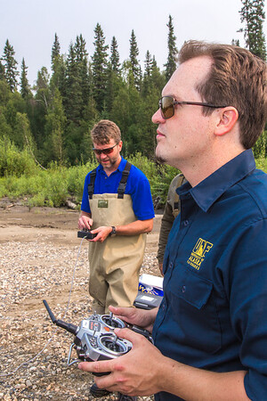 Jimmy Fox, deputy field supervisor with the U.S. Fish and Wildlife Service, and pilot Trevor Parcell with the Alaska Center for Unmanned Aircraft Systems Integration (ACUASI) operate an unmanned aerial vehicle from a gravel bar along a stretch of the upper Chena River in an effort to collect aerial video of prime king salmon spawning habitat.  Filename: AAR-15-4593-217.jpg