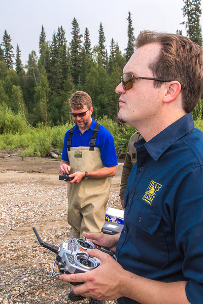 "Jimmy Fox, deputy field supervisor with the U.S. Fish and Wildlife Service, and pilot Trevor Parcell with the Alaska Center for Unmanned Aircraft Systems Integration (ACUASI) operate an unmanned aerial vehicle from a gravel bar along a stretch of the upper Chena River in an effort to collect aerial video of prime king salmon spawning habitat.  <div class=""ss-paypal-button"">Filename: AAR-15-4593-217.jpg</div><div class=""ss-paypal-button-end""></div>"