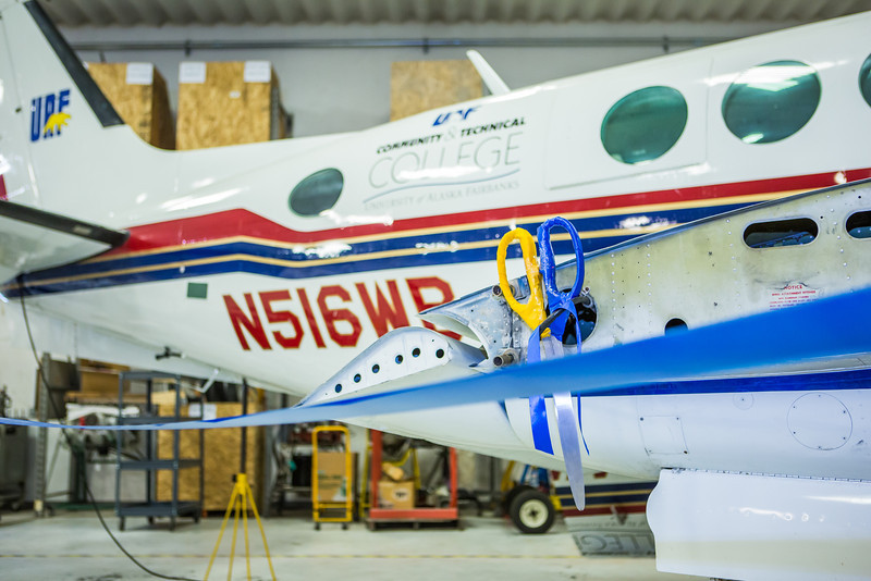 """A pair of giant scissors hangs from a wing of an airplane before the official ribbon cutting ceremony in CTC's new aviation program hanger at the Fairbanks International Airport.  <div class=""""ss-paypal-button"""">Filename: AAR-13-3810-6.jpg</div><div class=""""ss-paypal-button-end"""" style=""""""""></div>"""