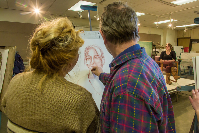 """Professor Todd Sherman, dean of UAF's College of Liberal Arts, works with one of his students in the portrait painting class during the 2014 Wintermester in the Fine Arts complex.  <div class=""""ss-paypal-button"""">Filename: AAR-14-4032-37.jpg</div><div class=""""ss-paypal-button-end"""" style=""""""""></div>"""