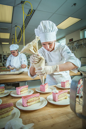 Stephanie Valentik applies whipped cream to a batch of raspberry tarts being served during lunch at CTC's culinary arts kitchen in the Hutchison Center.  Filename: AAR-13-3811-154.jpg