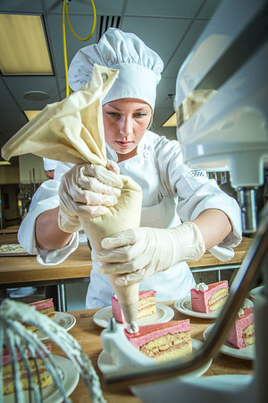 Stephanie Valentik applies whipped cream to a batch of raspberry tarts being served during lunch at CTC's culinary arts kitchen in the Hutchison Center.  Filename: AAR-13-3811-153.jpg