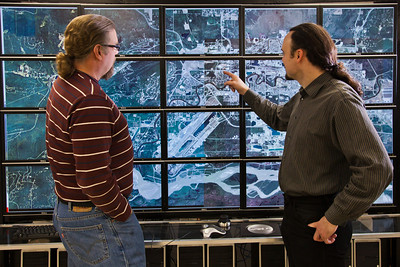 Computer science faculty members Jon Genetti, left, and Orion Lawlor inspect a high resolution aerial photo of Fairbanks on the bioinformatics powerwall in the Chapman Building.  Filename: AAR-12-3272-142.jpg