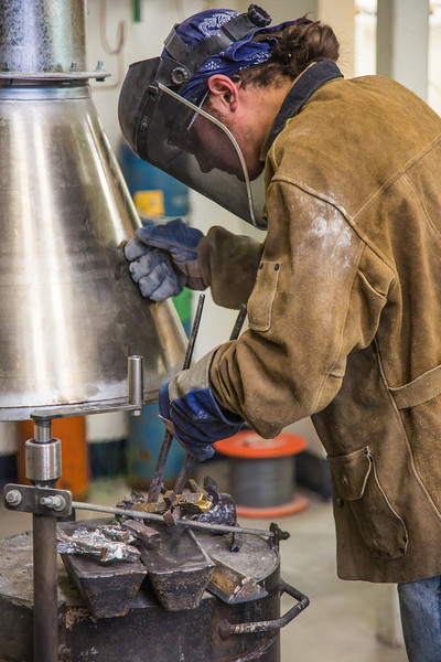 """Art major Joel Isaak positions equipment prior to pouring molten bronze as part of the process of creating a life-sized sculpture for his senior thesis in the UAF Fine Arts complex.  <div class=""""ss-paypal-button"""">Filename: AAR-12-3347-006.jpg</div><div class=""""ss-paypal-button-end"""" style=""""""""></div>"""