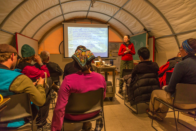 """Assistant professor Donie Bret-Harte presents a lecture to visiting students at the presentation tent at the Toolik Field Station on Alaska's North Slope. Bret-Harte serves as chief science officer at the facility, operated by UAF's Institute of Arctic Biology.  <div class=""""ss-paypal-button"""">Filename: AAR-14-4216-022.jpg</div><div class=""""ss-paypal-button-end""""></div>"""