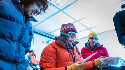 Assistant professor of geophysics Erin Pettit, center, cuts slices of glacier samples in the Elvey Building's ice lab.  Filename: AAR-12-3330-015.jpg