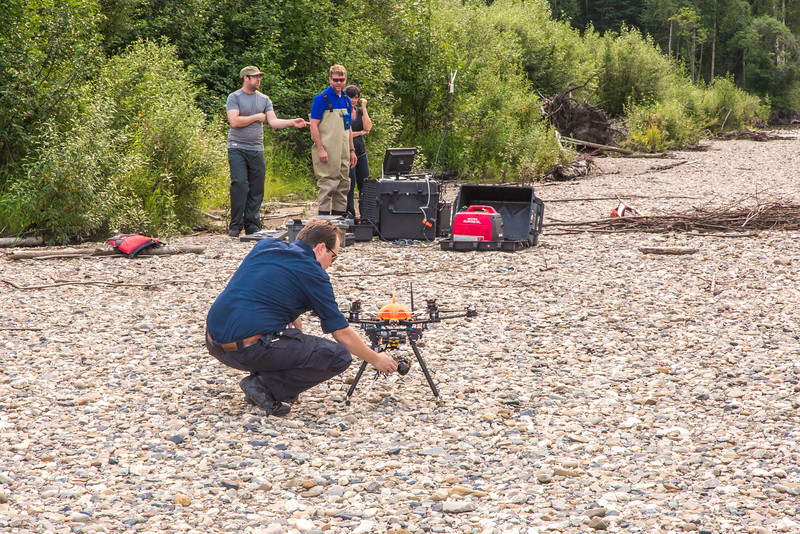 """Personnel with the U.S. Fish and Wildlife Service and the Alaska Center for Unmanned Aircraft Systems Integration (ACUASI) establish a piloting station on a gravel bar along a stretch of the upper Chena River in an effort to collect aerial video of prime king salmon spawning habitat.  <div class=""""ss-paypal-button"""">Filename: AAR-15-4593-196.jpg</div><div class=""""ss-paypal-button-end""""></div>"""