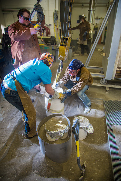 """Art major Joel Isaak get some help from student volunteers to position his plaster molds prior to pouring molten bronze as part of the process of creating a life-sized sculpture for his senior thesis in the UAF Fine Arts complex.  <div class=""""ss-paypal-button"""">Filename: AAR-12-3347-015.jpg</div><div class=""""ss-paypal-button-end"""" style=""""""""></div>"""