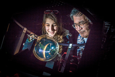 Physics major Haley Nelson, left, and Stanley Edwin experiment with a device that creates an artificial aurora borealis in a Reichardt Building lab.  Filename: AAR-13-4009-71.jpg