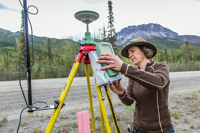 Associate professor Margaret Darrow installs a GPS tracking module along the Dalton Highway about 225 miles north of Fairbanks. Darrow and a team of state geologists are tracking movement on a series of frozen debris lobes which have appeared along the Dietrich River valley in the southern Brooks Range, which could threaten the highway and the nearby trans-Alaska pipeline.  Filename: AAR-14-4214-12.jpg