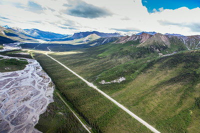 This photo shows a couple of several frozen debris lobes which are moving at various speeds down the hillsides along the Dietrich River valley in the southern Brooks Range, posing a serious threat to the Dalton Highway and Trans-Alaska Pipeline.  Filename: AAR-14-4219-112.jpg