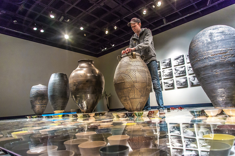 """Art major Ian Wilkinson adjusts one of his ceramic pieces in the UAF Fine Arts gallery. His BFA thesis project, Spheres of Influence, raised more than $18,000 for the Fairbanks Food Bank through the sale of his 1,200 bowls.  <div class=""""ss-paypal-button"""">Filename: AAR-13-3775-6.jpg</div><div class=""""ss-paypal-button-end"""" style=""""""""></div>"""