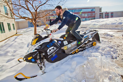 Engineering major Isaac Thompson drives the electric snowmachine he and other members of his team helped modify into the Duckering Building after its return to campus after claiming the top prize in the SAE Clean Showmobile Challenge in Houghton, Mich.  Filename: AAR-12-3337-42.jpg