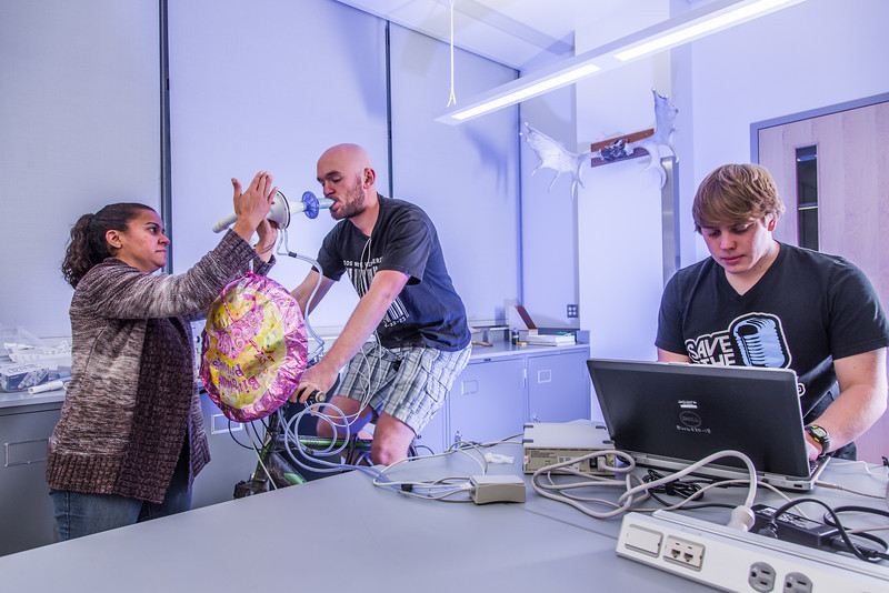 "Ivan Lien works out on his bicycle while Marisol Bastiani, left, and Chris Wilson collect data measuring his respiration during a human physiology lab in the Murie Building.  <div class=""ss-paypal-button"">Filename: AAR-13-3983-54.jpg</div><div class=""ss-paypal-button-end"" style=""""></div>"