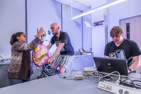 """Ivan Lien works out on his bicycle while Marisol Bastiani, left, and Chris Wilson collect data measuring his respiration during a human physiology lab in the Murie Building.  <div class=""""ss-paypal-button"""">Filename: AAR-13-3983-54.jpg</div><div class=""""ss-paypal-button-end"""" style=""""""""></div>"""