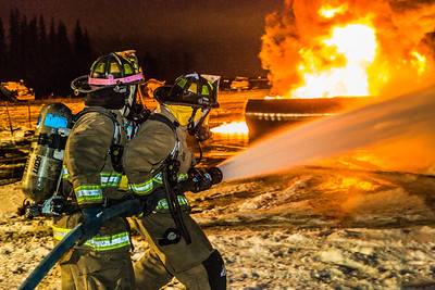 Student firefighters with the University Fire Department spray water on a blaze of burning fuel during a live training drill at the Fairbanks International Airport.  Filename: AAR-13-3995-209.jpg