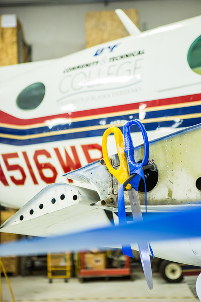 """A pair of giant scissors hangs from a wing of an airplane before the official ribbon cutting ceremony in CTC's new aviation program hanger at the Fairbanks International Airport.  <div class=""""ss-paypal-button"""">Filename: AAR-13-3810-1.jpg</div><div class=""""ss-paypal-button-end"""" style=""""""""></div>"""