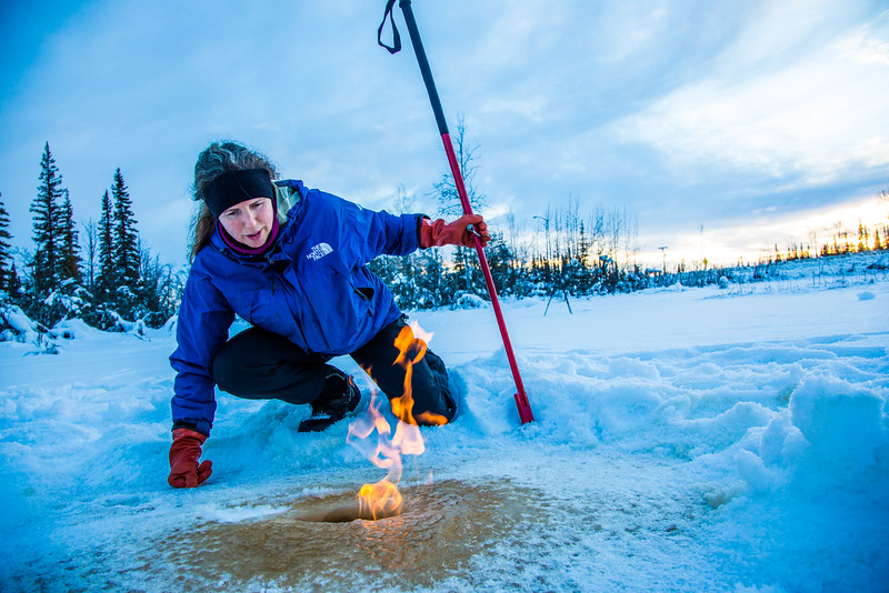 """Research Associate Professor Katey Walter Anthony inspects flaming methane gas seeping from a hole in the ice on the surface of a pond on the UAF campus. The naturally occurring phenomenon is made worse by thawing permafrost and increased plant decay caused by global warming.  <div class=""""ss-paypal-button"""">Filename: AAR-16-4815-36.jpg</div><div class=""""ss-paypal-button-end""""></div>"""