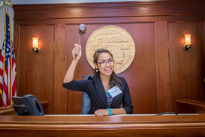 Malorie Johnson, a senior in UAF's rural development program from Unalakleet, has some fun with the gavel moments after posing with Speaker Mike Chenault in the House chambers during a weeklong seminar on understanding the legislative process in Juneau.  Filename: AAR-14-4053-167.jpg