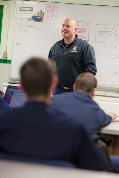 """Captain Forrest Kuiper leads a post-operation debriefing in the University Fire Department's dining hall in the Whitaker Building on the Fairbanks campus.  <div class=""""ss-paypal-button"""">Filename: AAR-11-3223-04.jpg</div><div class=""""ss-paypal-button-end"""" style=""""""""></div>"""