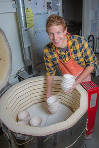 Art major Ian Wilkinson unloads a kiln after a bisque firing for some of the approximately 1,000 ceramic bowls needed for his senior thesis project in the fine arts complex on the Fairbanks campus.  Filename: AAR-12-3547-075.jpg