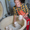 "Art major Ian Wilkinson unloads a kiln after a bisque firing for some of the approximately 1,000 ceramic bowls needed for his senior thesis project in the fine arts complex on the Fairbanks campus.  <div class=""ss-paypal-button"">Filename: AAR-12-3547-075.jpg</div><div class=""ss-paypal-button-end"" style=""""></div>"