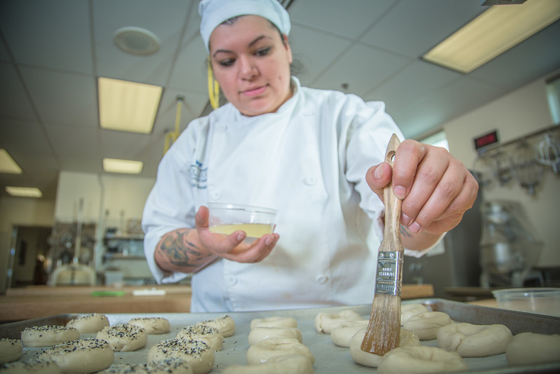 "Charlotte Gordon applies an egg wash to mini-bagels served during lunch at CTC's culinary arts kitchen in the Hutchison Center.  <div class=""ss-paypal-button"">Filename: AAR-13-3811-146.jpg</div><div class=""ss-paypal-button-end"" style=""""></div>"