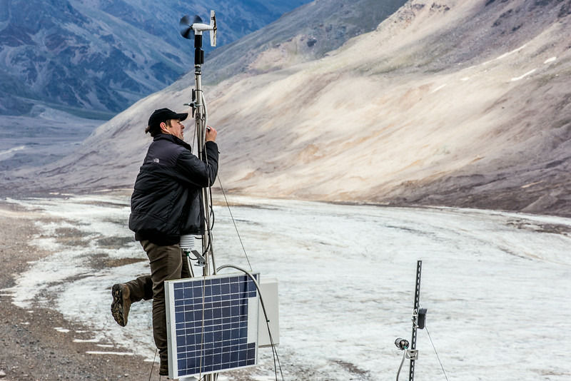 """Joel Bailey, a research professional with UAF's Institute of Northern Engineering, secures connections on a data collecting station above the surface of the Jarvis Glacier in the eastern Alaska Range.  <div class=""""ss-paypal-button"""">Filename: AAR-14-4256-281.jpg</div><div class=""""ss-paypal-button-end""""></div>"""
