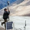 "Joel Bailey, a research professional with UAF's Institute of Northern Engineering, secures connections on a data collecting station above the surface of the Jarvis Glacier in the eastern Alaska Range.  <div class=""ss-paypal-button"">Filename: AAR-14-4256-281.jpg</div><div class=""ss-paypal-button-end""></div>"