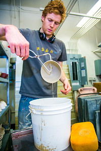 Art major Ian Wilkinson dips one of the 1,000--plus same-sized bowls into a bucket of glaze before stacking them ina kiln in the UAF ceramics studio.  Filename: AAR-13-3752-49.jpg