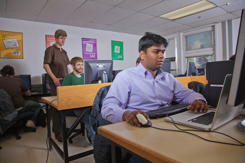 """Faculty member John Quan, standing, provides assistance to one of his students in the Chapman Building ASSERT lab.  <div class=""""ss-paypal-button"""">Filename: AAR-12-3272-76.jpg</div><div class=""""ss-paypal-button-end"""" style=""""""""></div>"""