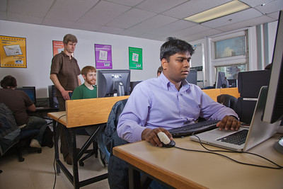 Faculty member John Quan, standing, provides assistance to one of his students in the Chapman Building ASSERT lab.  Filename: AAR-12-3272-76.jpg
