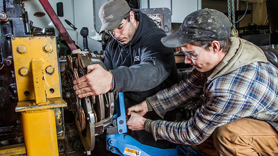 Tony Craig, left, and George Jensen work together disassembling a transmission in the diesel mechanics lab at the Hutchison Institute of Technology.  Filename: AAR-12-3312-094.jpg