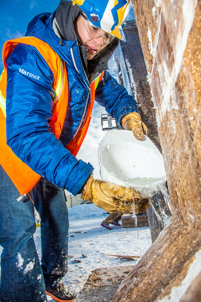 """Engineering major Ryan Cudo pours water which will freeze and help stablize the vertical supports during the raising of the 2013 ice arch in Cornerstone Plaza on the Fairbanks campus. Students this year built the structure out of a mixture of ice and sawdust, which is many times stronger than concrete.  <div class=""""ss-paypal-button"""">Filename: AAR-13-3736-102.jpg</div><div class=""""ss-paypal-button-end"""" style=""""""""></div>"""