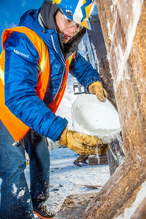 Engineering major Ryan Cudo pours water which will freeze and help stablize the vertical supports during the raising of the 2013 ice arch in Cornerstone Plaza on the Fairbanks campus. Students this year built the structure out of a mixture of ice and sawdust, which is many times stronger than concrete.  Filename: AAR-13-3736-102.jpg