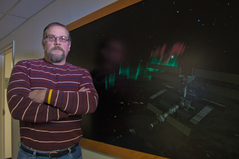 """Computer Science Associate Professor Jon Genetti poses by an illustration in a Chapman Building hallway.  <div class=""""ss-paypal-button"""">Filename: AAR-12-3272-90.jpg</div><div class=""""ss-paypal-button-end"""" style=""""""""></div>"""