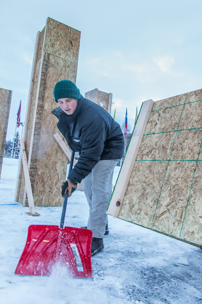 """Engineering major Tripp Collier clears snow from underneath forms used to hold the foundation during initial contruction of the 2014 ice arch, a tradition on the UAF campus for more than 50 years.  <div class=""""ss-paypal-button"""">Filename: AAR-14-4031-50.jpg</div><div class=""""ss-paypal-button-end""""></div>"""