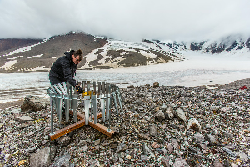 "Matvey Debolskiy, a Ph.D. student in geophysics, balances a precipitation gauge on a ridge above the Jarvis Glacier in the eastern Alaska Range.  <div class=""ss-paypal-button"">Filename: AAR-14-4256-301.jpg</div><div class=""ss-paypal-button-end""></div>"