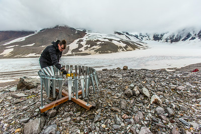 Matvey Debolskiy, a Ph.D. student in geophysics, balances a precipitation gauge on a ridge above the Jarvis Glacier in the eastern Alaska Range.  Filename: AAR-14-4256-301.jpg