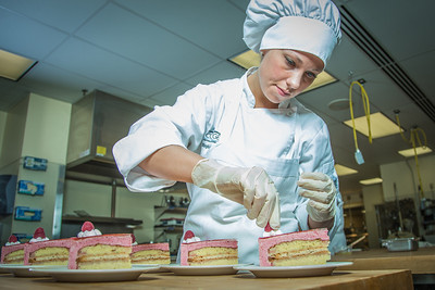 Stephanie Valentik applies fresh berries to a batch of raspberry tarts being served during lunch at CTC's culinary arts kitchen in the Hutchison Center.  Filename: AAR-13-3811-170.jpg