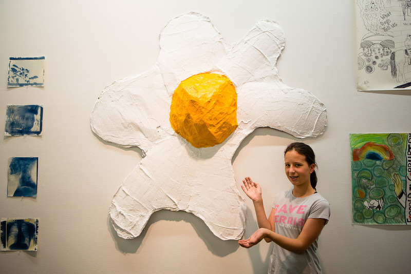 """Emilia Helms-Leslie poses next to her sculpture of a large fried egg made out of shaped cardboard, plaster, and paint during UAF's Visual Arts Academy show at the Art Gallery.  <div class=""""ss-paypal-button"""">Filename: AAR-12-3436-7.jpg</div><div class=""""ss-paypal-button-end"""" style=""""""""></div>"""