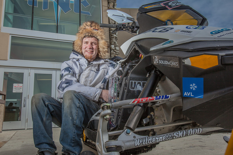 """Mechanical enineering major Isaac Thompson poses with the UAF team's snowmobile in front of the Duckering Building after its return from competing in the Society of Automotive Engineers' Clean Snowmobile Challenge in Houghton, Mich.  <div class=""""ss-paypal-button"""">Filename: AAR-12-3345-087.jpg</div><div class=""""ss-paypal-button-end"""" style=""""""""></div>"""