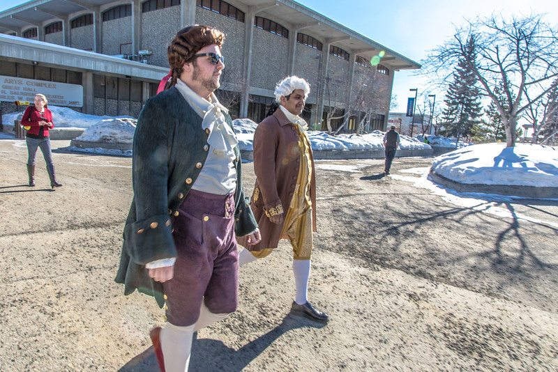 """Brian Tuohy, playing the title role in Theatre UAF's production of """"Tartuffe,"""" (left) and Sambit Misra, playing Orgon, walk across campus before performing a live teaser in Wood Center a couple of days before opening night.  <div class=""""ss-paypal-button"""">Filename: AAR-14-4121-17.jpg</div><div class=""""ss-paypal-button-end"""" style=""""""""></div>"""