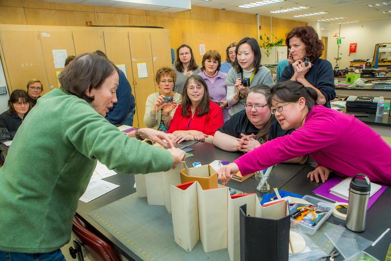 """Students react as instructor Margo Klass shows off finished projects in a custom book binding workshop offered by UAF Summer Sessions during Wintermester 2013.  <div class=""""ss-paypal-button"""">Filename: AAR-13-3706-37.jpg</div><div class=""""ss-paypal-button-end"""" style=""""""""></div>"""