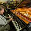 "UAF Professor Eduard Zilberkant plays on the Yamaha disklavier temporarily stored in his office. The instrument is being used in the summer of 2014 for the international piano e-competition hosted on the Fairbanks campus.  <div class=""ss-paypal-button"">Filename: AAR-14-4179-18.jpg</div><div class=""ss-paypal-button-end""></div>"