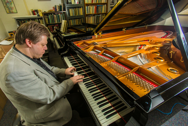"""UAF Professor Eduard Zilberkant plays on the Yamaha disklavier temporarily stored in his office. The instrument is being used in the summer of 2014 for the international piano e-competition hosted on the Fairbanks campus.  <div class=""""ss-paypal-button"""">Filename: AAR-14-4179-18.jpg</div><div class=""""ss-paypal-button-end""""></div>"""